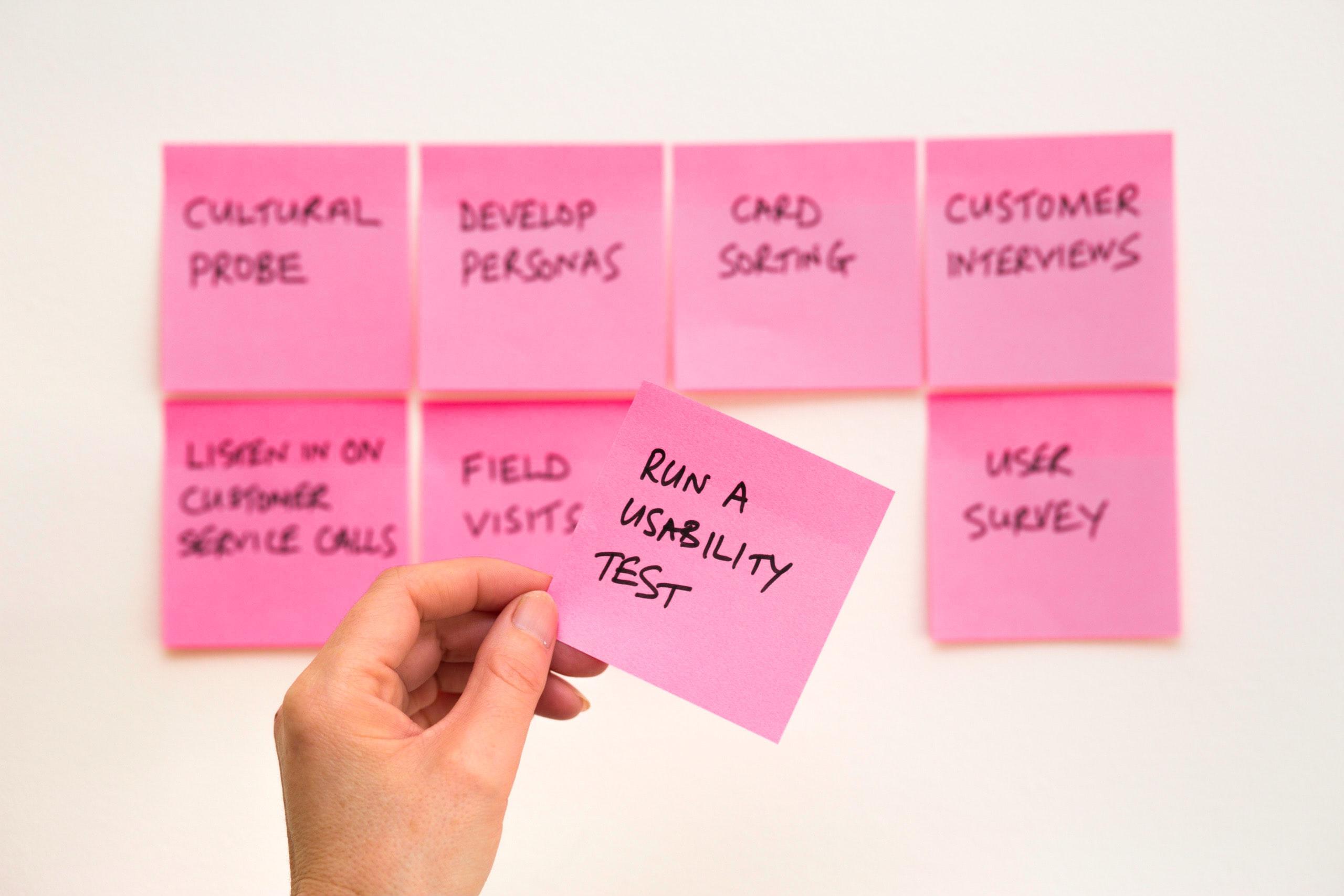 Imagem com papéis adesivos colados à parede com os nomes das ferramentas e método de Usabilidade.